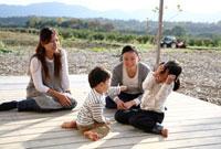 ウッドデッキで遊ぶ2組の母親と子供