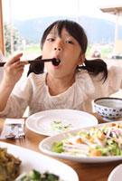 おかずを頬張る女の子 22600005844| 写真素材・ストックフォト・画像・イラスト素材|アマナイメージズ