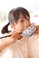 ご飯を頬張る女の子 22600005845| 写真素材・ストックフォト・画像・イラスト素材|アマナイメージズ