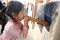 かまどの火を筒で吹く女の子 22600005850| 写真素材・ストックフォト・画像・イラスト素材|アマナイメージズ