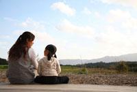 田園風景を望む後姿の母親と女の子