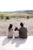 田園風景を望む後姿の3人家族