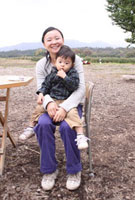 子供を膝に乗せ屋外の椅子に座る母親