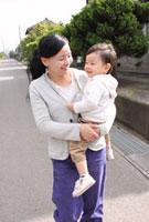 子供を抱え道路を歩く母親
