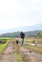 田園の畦道を駆ける女の子と父親 22600005869| 写真素材・ストックフォト・画像・イラスト素材|アマナイメージズ