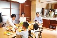 テーブルで食事をする3世代家族