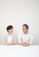 白壁の前に座るシニア夫婦