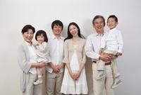 白壁の前の3世代家族