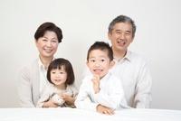 白壁の前に孫と座るシニア夫婦
