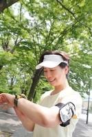 腕時計を見るジョギング姿のシニア女性