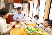 テーブルで孫と食事をするシニア夫婦