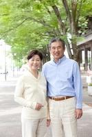 新緑の街で微笑むシニア夫婦