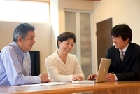 自宅で営業マンの説明を受けるシニア夫婦