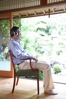 縁側に座り音楽を聴くシニア男性