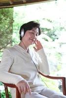 縁側に座り音楽を聴くシニア女性