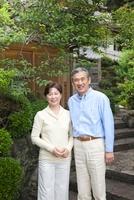 玄関前で微笑むシニア夫婦