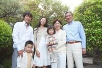 庭で微笑む3世代家族