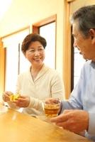 テーブルでお茶を飲むシニア夫婦