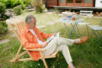 庭でくつろぐシニア男性