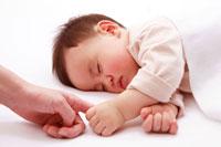 指を掴む寝ている赤ちゃん