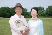 公園で犬を抱いているシニア夫婦