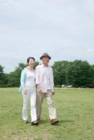 公園を散歩するシニア夫婦