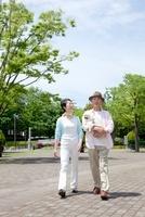 犬を抱いて公園を散歩するシニア夫婦