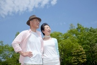 公園で風景を眺めているシニア夫婦
