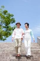 公園の階段を降りるシニア夫婦