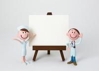 イーゼルのホワイトボードの脇に立つ医師と看護師