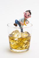 お酒のグラスに入ろうとしているヨッパライの男性