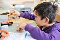 理科室で電磁石を組み立てる男の子