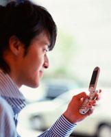 携帯電話でメールするビジネスマン