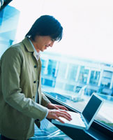 窓際でノートパソコンを広げるビジネスマン