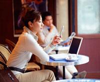 ノートパソコンの前で携帯電話を見るビジネスウーマン