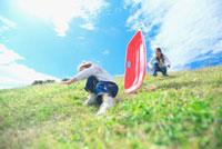 土手滑りをして遊ぶ親子