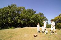 公園で犬と遊ぶ家族