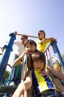 公園の滑り台で遊ぶ家族