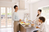 キッチンで料理をする夫婦と子供
