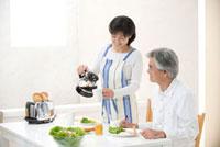 食卓で朝食を食べる中高年夫婦