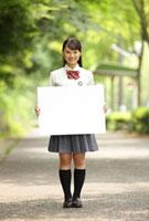 メッセージボードを持つ女子高生