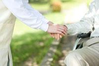 手を握る介護ヘルパーと車椅子のシニア男性