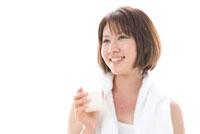 タンクトップ姿で歯を磨く女性
