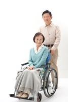 老人女性の車椅子を押す老人男性