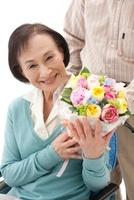 車椅子の老人女性に花束を渡す老人男性