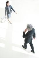 スーツケースをひくOLと携帯電話する中高年ビジネスマン