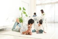 リビングルームでタブレットPCで遊ぶ父と娘の4人家族と犬 22933004114| 写真素材・ストックフォト・画像・イラスト素材|アマナイメージズ