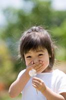 タンポポを持って口に手をあてて笑う少女
