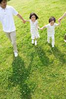 手をつないで草地を歩く親子 22946000899| 写真素材・ストックフォト・画像・イラスト素材|アマナイメージズ