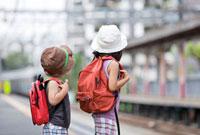 駅のホームで電車を待つ姉と弟の後ろ姿